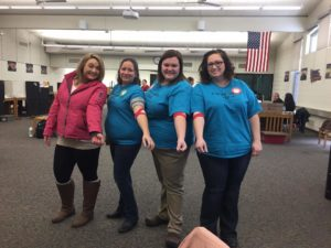 Sarah, Diana, Lynnsey, and Tosha with arms out showing bandage from blood drive