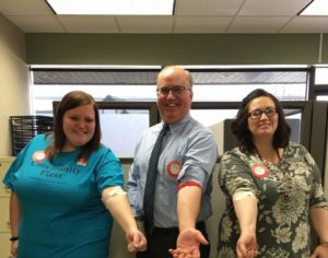 Lynnsey, Tim, Tosha with arms out showing bandage from blood drive